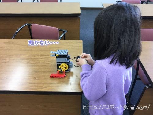 動かないロボットにがっかりの女の子