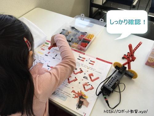 テキストを確認しながらロボット製作する子ども