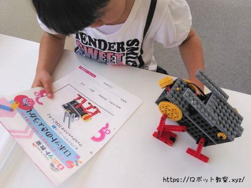 テキストを読みロボットを組み立てる子ども