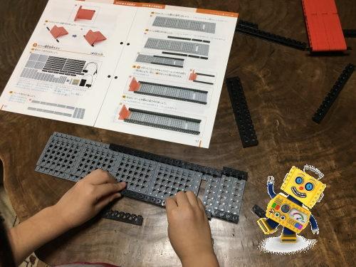 テキストを見ながらロボット作りする小学生