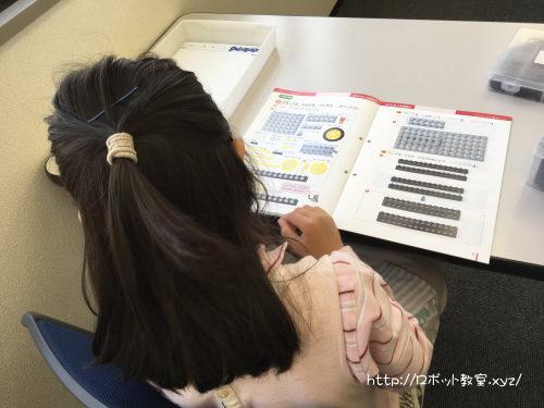 ロボット教室のテキストを読む小学1年生