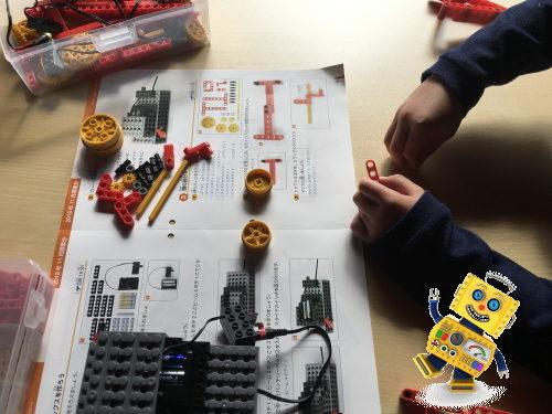 テキストをみてパーツを組み立てる小学生