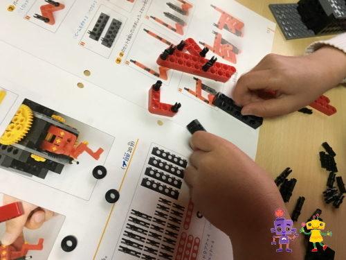 テキストをみながらロボットを組み立てする小学生